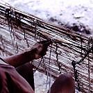 Waiwai woman weaving a hammock by jellyfish in Hammocks