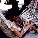 Waiwai woman sitting in a hammock while weaving a seed apron by jellyfish in Hammocks