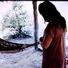 Waiwai woman adjusting her hammock suspension by jellyfish in Hammocks